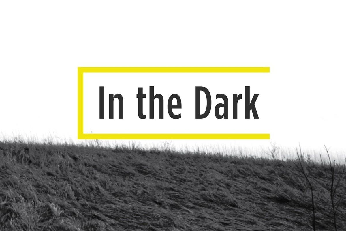 """in the dark"" in a yellow open ended box on a picture of a grassy hill"