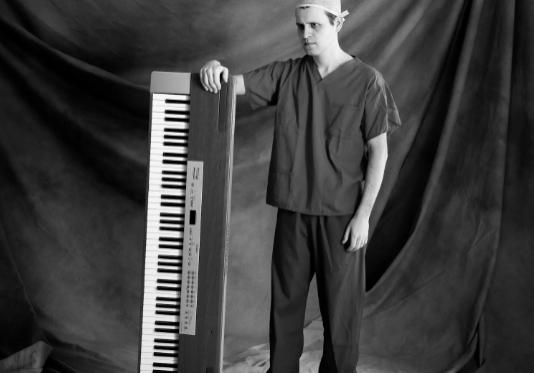 A man dressed like a surgon holding a keyboard on its side